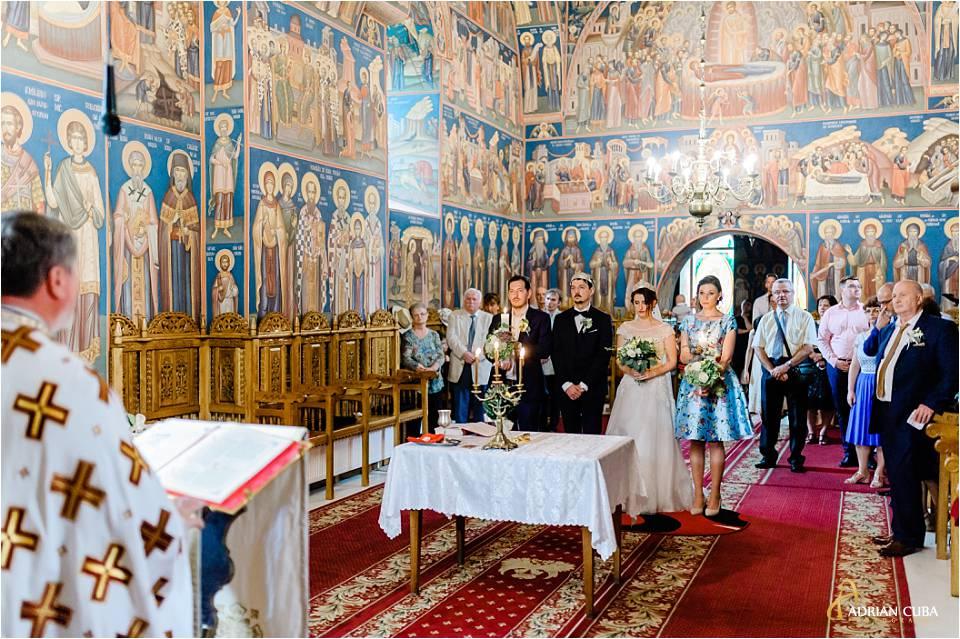 preotul vorbeste mirilor si invitatilor in biserica.