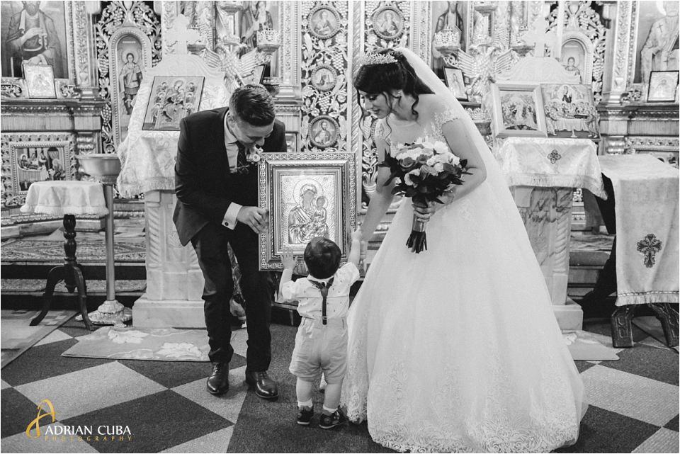 Un baietel saruta icoana alaturi de mire si mireasa la biserica Sfantul Nicolae din Vaslui.